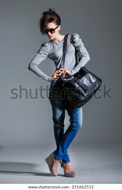Portrait of stylish woman holding bag in sunglasses posing on gray backgroud