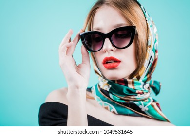 bbed5597f3 Portrait of a stylish woman posing in sunglasess and scarf on head,  isolated on blue