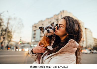 Portrait of a stylish woman standing with a dog in her arms on a background of cityscape, looking to the side. Walk with your pet in the evening city.