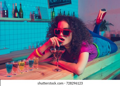 portrait of stylish woman in sunglasses lying on counter and drinking cocktail in bar