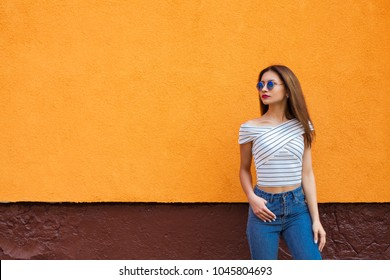 Portrait of stylish woman in sunglasses with make-up and flying hairs. Urban