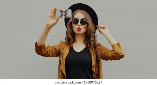 Portrait-stylische Frau, die sich selbst fotografiert, mit Smartphone mit schwarzem Hut, Sonnenbrille, brauner Jacke mit lockigem Haar auf grauem Hintergrund