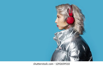 Portrait of stylish young blonde female posing in profile. Caucasian girl in jacket wearing headphones. Music and style concept. Copy space in left side. Isolated on blue background
