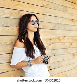 Portrait of stylish young brunette woman in casual clothes with old camera wearing sunglasses