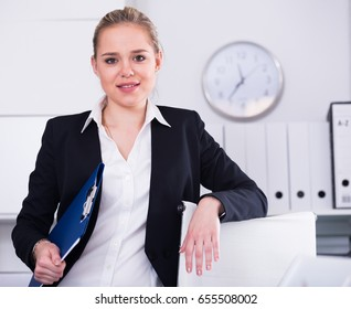 Portrait of stylish young business woman standing in office holding clipboard