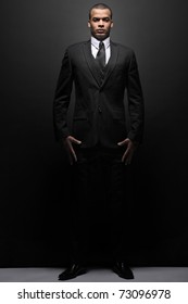 Portrait of a stylish young businessman in a black suit.