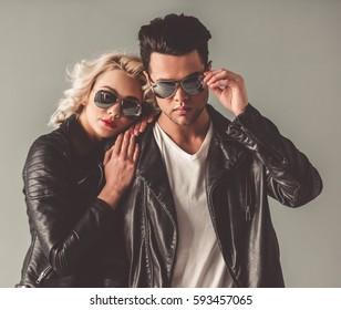 Portrait of stylish young couple in leather jackets and sun glasses, on gray background