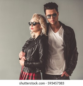 Portrait of stylish young couple in leather jackets and sun glasses hugging, on gray background