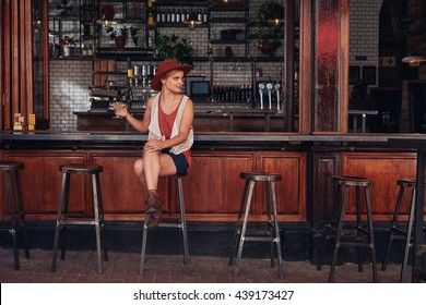 Portrait of stylish young female sitting at a cafe with drink and looking away. Beautiful caucasian female at coffee shop counter.