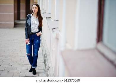 Portrait of stylish young girl wear on leather jacket and ripped jeans with mobile phone at hand. Street fashion model style.