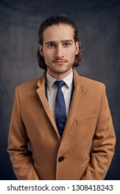 Portrait of a stylish young handsome long-haired unshaven man in light brown blazer and blue necktie, looking at camera with friendly face