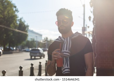 Portrait of a stylish young hipster arab male with juice. Urban holiday at the weekend concept.