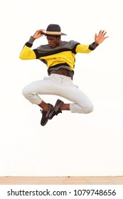 Portrait of stylish young male dancer jumping and showing his moves on white background