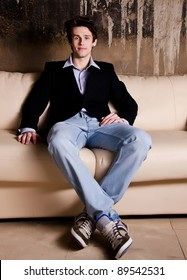 Portrait of stylish young man relaxing on couch at home