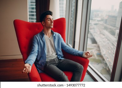 Portrait of stylish young man sitting in chair and meditate