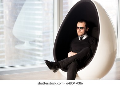Portrait of stylish young man in sunglasses wearing white shirt with tie under black jumper sitting in luxury egg armchair near window. Confident head of company dreaming about leadership in business