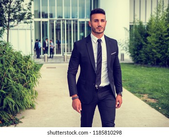Portrait of stylish young man wearing business suit, standing in modern city setting