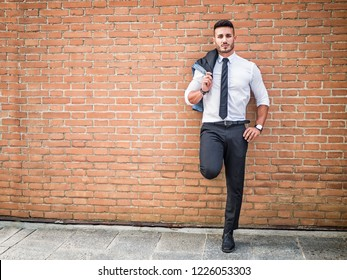 Portrait of stylish young man wearing business suit, standing in modern city setting, leaning against brick wall