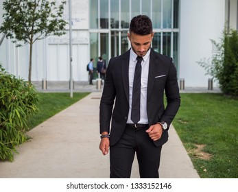 Portrait of stylish young man wearing business suit, standing in modern city setting, looking down