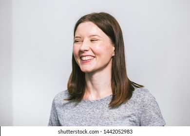 portrait of stylish young pretty Caucasian woman smiling in grey t-shirt on white studio background, isolated, natural look, long brown hair.