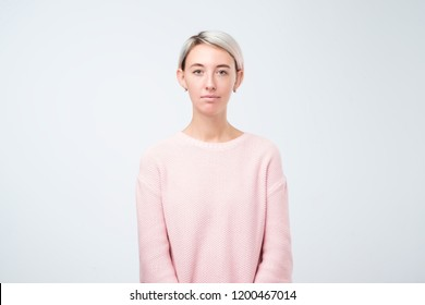 portrait of stylish young pretty woman smiling standing in pink sweater on white studio background. Simple not emotional face