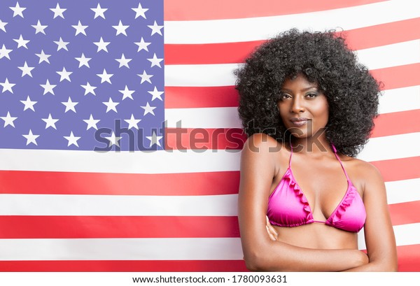 Portrait of stylish young woman in bikini standing against American flag