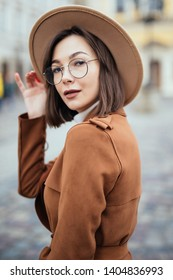Portrait of stylish young woman in coat and hat looking away and keeping hand in pocket while standing on city street. Beautiful hipster girl in eyeglasses posing on balcony outdoors. City style