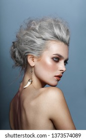 Portrait of stylish young woman with gray hairstyle, smokey eyes and perfect skin and beautiful makeup with naked shoulders, with earring in the ear, looking at one side, isolated on blue background.