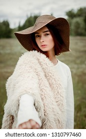 portrait stylish young woman in hat posing outdoors