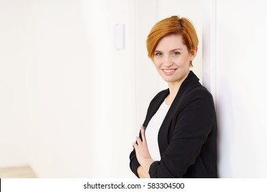 Portrait of stylish young woman with short hair standing over white office background with her arms crossed, looking at camera and smiling happily. Copy space