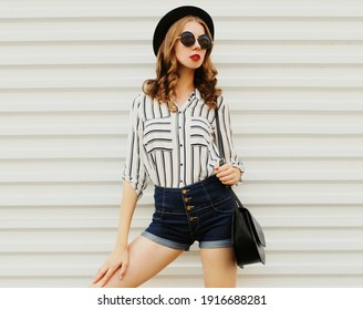 Portrait of stylish young woman wearing a striped shirt and black round hat on a white background