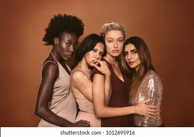 Portrait of stylish young women standing over brown background. Multi ethnic fashion models posing together in studio.