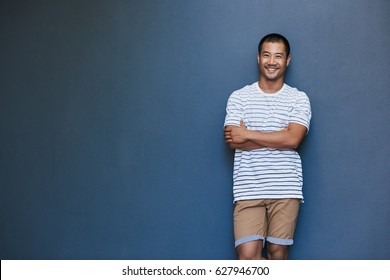 Portrait of a stylishly dressed smiling young Asian man leaning with his arms crossed against a gray wall outside