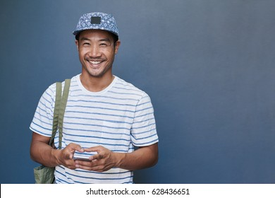 Portrait of a stylishly dressed smiling young Asian man sending text messages on his cellphone while standing against a gray wall outside