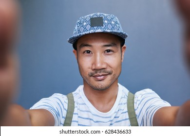 Portrait of a stylishly dressed young Asian man taking a selfie while standing alone in front of a gray wall outside