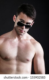 Portrait of stylized young man wearing sunglasses black background