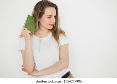 Portrait of succesful smiling woman in casual wear with green book on light background.
