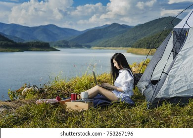 Portrait of succesful woman with laptop near camp tent outdoors