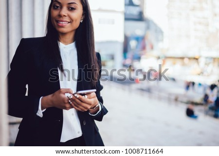 01168226b49 Portrait of successful African American female entrepreneur dressed in  stylish formal suit holding smartphone device while