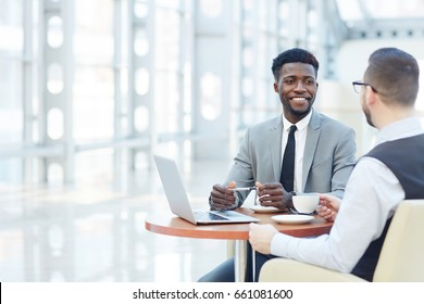 Portrait of successful African-American businessman smiling during meeting with colleague at coffee break