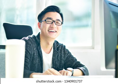 portrait of successful asian business man working in office looking at camera smiling