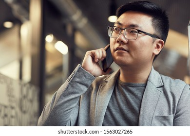 Portrait of successful Asian businessman speaking by phone while standing in modern office interior, copy space