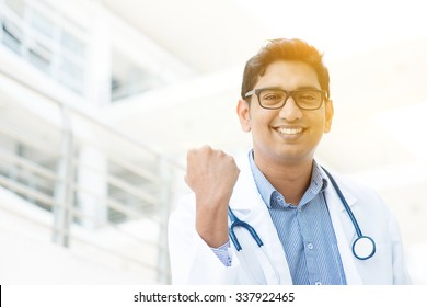 Portrait of successful Asian Indian medical doctor smiling and celebrating success, standing outside hospital building, beautiful golden sunlight at background.