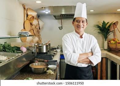 Portrait of successful Asian mature chef standing with arms crossed and smiling at camera while standing in modern kitchen