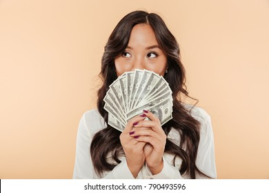 Portrait of successful asian woman covering mouth with fan of 100 dollar bills being satisfied about salary or income, posing over beige background