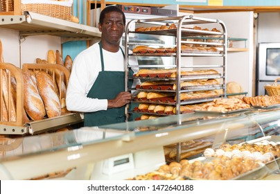 Portrait of successful baker during daily work behind counter in small bakeshop