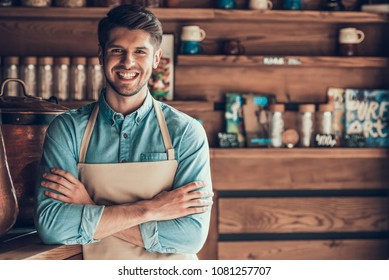 Portrait of successful barista in apron in cafe. Young entrepreneur in coffee shop.