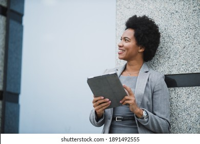 Portrait of a successful black business woman using digital tablet during quick break in front a corporate building.