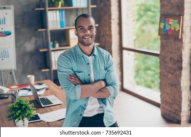 Portrait of successful black guy, looking at the camera, standing with crossed arms at his work place in the office, in casual smart, smiling