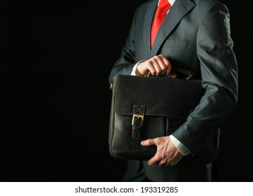 Portrait of successful business man with bag isolated on black background
